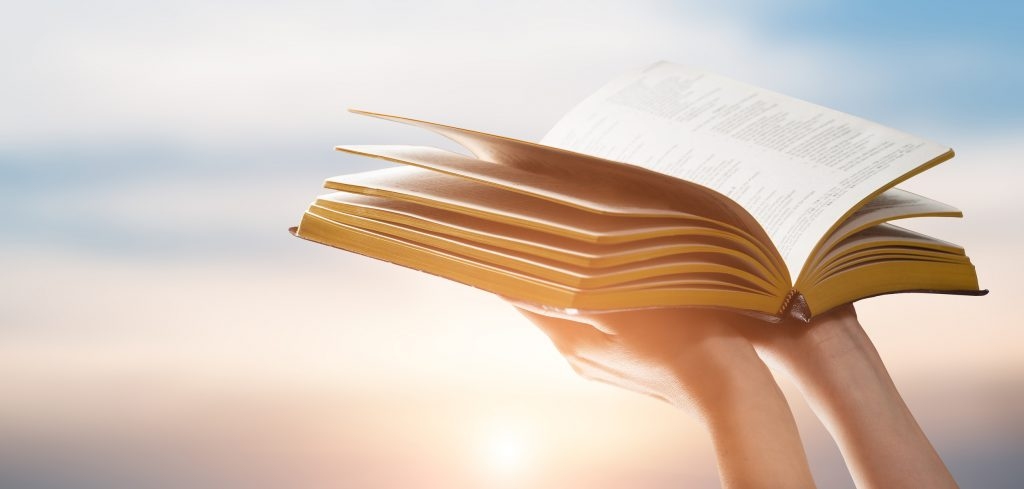 Person holding bible at Sunset